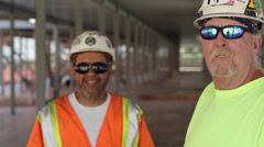 Construction workers wearing sunglasses giving thumbs up with one worker in Stock Footage