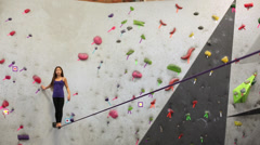 Stock Video Footage of Mixed race girl walking on slackline at indoor climbing gym