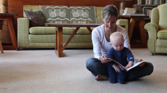 Caucasian mother sitting on floor reading to baby boy Stock Footage