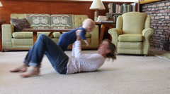 Caucasian mother laying on floor lifting baby boy Stock Footage
