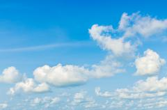 Puffy clouds and blue sky in sunny day Stock Photos
