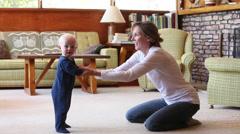 Caucasian mother kneeling on floor encouraging baby boy to walk Stock Footage