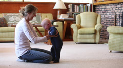 Caucasian mother kneeling on floor encouraging baby boy to walk Stock Footage