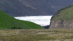 Glacier view thru green valley, moraines in foreground Stock Footage