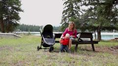 Caucasian girl helps baby boy walk in park Stock Footage