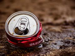 Crushed Red Soda Can on Ground - stock photo