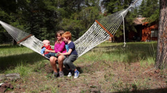 Caucasian boy and girl with baby boy swinging in hammock Stock Footage