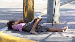 Beggar child sleeping on the street in Cebu city, Philippines Stock Footage