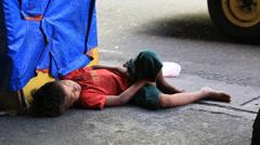 Beggar boy sleeping on the street in Cebu city, Philippines Stock Footage