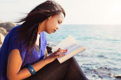 Young girl studying her bible by the sea Stock Photos