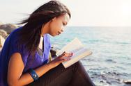 Stock Photo of young girl studying her bible by the sea