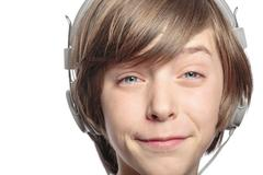 male teenager with headphones hurts the music, isolated on white - stock photo