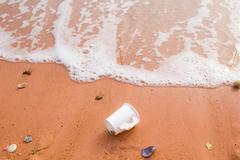Discarded paper cup in the sand Stock Photos