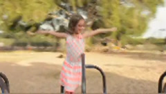 Hispanic girl with red eyeglasses spinning on merry-go-round Stock Footage