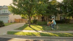 Hispanic woman riding bicycle with groceries through neighborhood Stock Footage