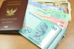thailand passport and ringgit malaysia, yen japan - stock photo
