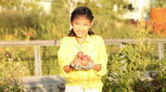 Asian girl showing her freshly-picked potatoes to the camera Stock Footage