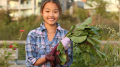 Smiling Japanese girl holding bunch of beets Stock Footage