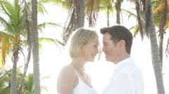 Caucasian couple hugging near palm trees Stock Footage