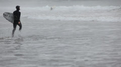 Surfers in wet suits in stormy ocean Stock Footage
