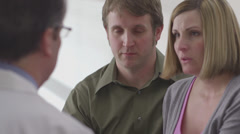 Caucasian doctor speaking with concerned couple Stock Footage