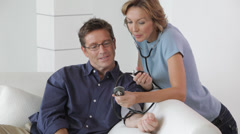 Caucasian woman checking husband's blood pressure Stock Footage