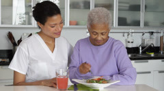 Senior woman with caregiver eating salad Stock Footage