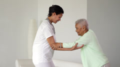 Nurse helping senior woman to walk Stock Footage