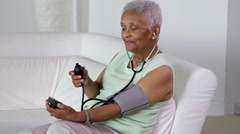Senior African American woman checking her blood pressure Stock Footage