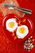 fried egg with heart shape yolks and rose tea - stock photo