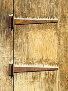 Rusty hinges on an old wooden door - stock photo