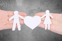 Paper family in hand with a big hearth isolated on white Stock Photos
