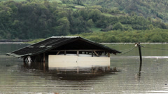 Flooded wooden hut in the lake water after big storm, beautiful landscape. Stock Footage
