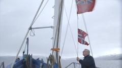 Fisherman hoists flag. Stock Footage