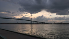 Dark storm clouds approach Ambassador bridge at Canada US border Stock Footage