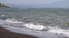 Black volcanic sand and water waves on the beach in Legazpi, Philippines Stock Footage