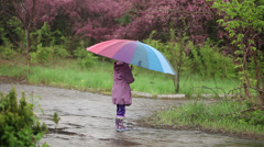 Little girl with an umbrella in the rain in the park. Child spinning  - stock footage
