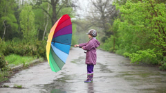 Rain. Happy little girl with umbrella in hands spinning on rain Stock Footage
