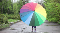Cheerful little girl hiding behind umbrella in the park. Thumbs up - stock footage