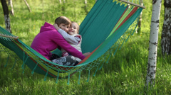 Happy mother and daughter hugging and sitting in a hammock outdoor Stock Footage