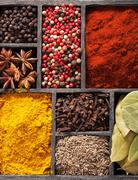 spices in box: pink  black pepper, paprika powder, curry, bay leaf; anise; cl - stock photo