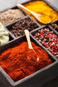Spices in box: pink  black pepper, paprika powder, curry, bay leaf; anise; cl Stock Photos