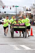 clergymen push holy rollers bed in annual fundraiser race - stock photo