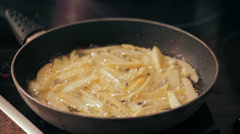 French fries cooking in boiling oil (with perforated spoon) - stock footage