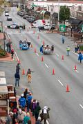 two teams race beds on city street in fundraiser event - stock photo