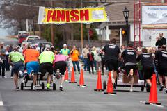 Two teams race beds to finish line in fundraiser Stock Photos
