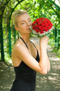 beautiful blond girl scenting bouquet of red roses - stock photo