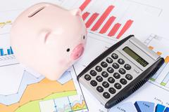 Stock Photo of piggy bank and calculator with  business charts