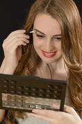 Attractive woman applying eyeshadow Stock Photos