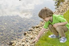 Kid playing with pebbles at lake - stock photo